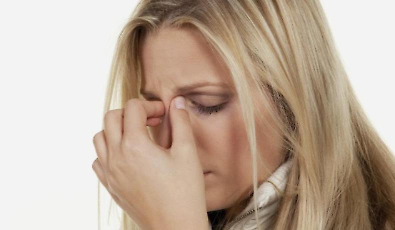 Frau mit Sinusitis-Symptomen im Bereich der Stirnhöhlen